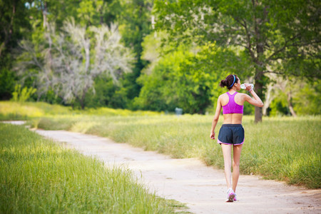 physically fit: Young woman walking on path drinking mineral water