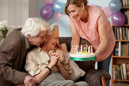 give out: Daughter giving birthday cake to senior mother LANG_EVOIMAGES
