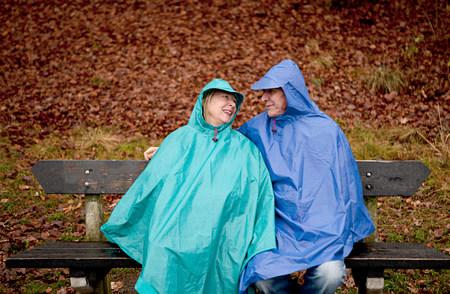 60 65 years: Senior couple sitting on park bench wearing waterproofs