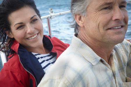 high winds: Mature couple sailing,close up