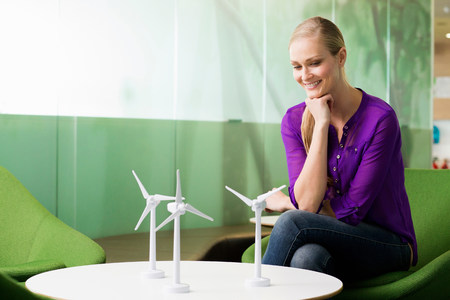 Young woman looking at model of wind turbine LANG_EVOIMAGES