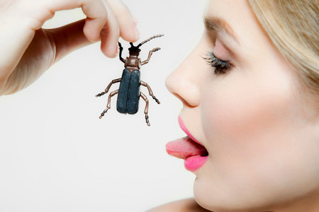revulsion: Young woman eating plastic beetle