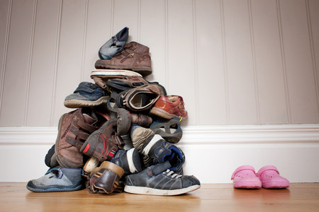 Large pile of boys shoes beside one pair of girls shoes LANG_EVOIMAGES