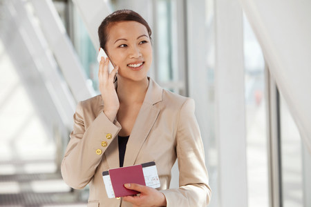 Businesswoman on cell phone with airline ticket and passport