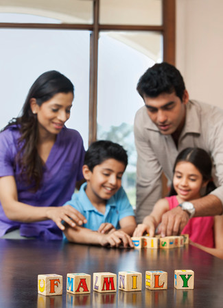 woman hanging toy: Family playing with building blocks