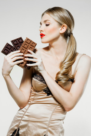 unfit: Young woman holding chocolate LANG_EVOIMAGES