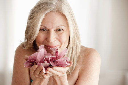 Mature woman holding flower,portrait