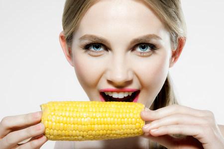 tempted: Young woman biting corn cob
