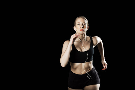exerting: Athlete running wearing earphones