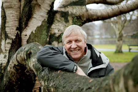 headshots: Senior man leaning against tree,smiling