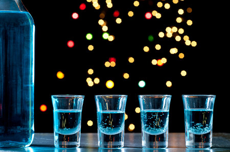 inebriated: Bottle and shots of blue alcohol