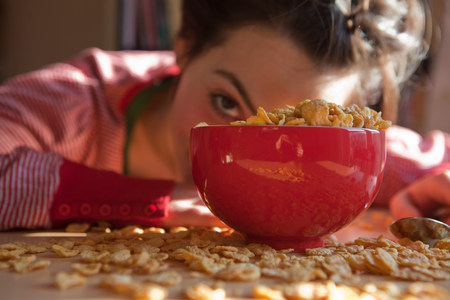 Young woman looking out from behind bowl and spilt breakfast cereal