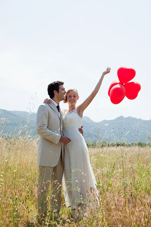 Newlyweds in field with red heart shape balloons LANG_EVOIMAGES
