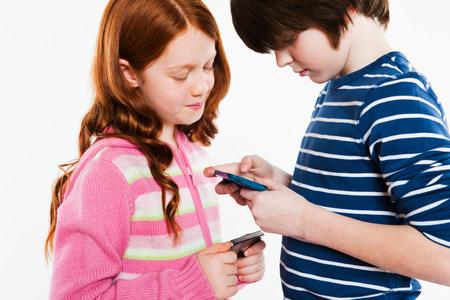Children looking a smartphones LANG_EVOIMAGES