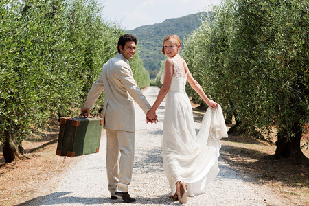Newlyweds walking on country road with suitcase LANG_EVOIMAGES