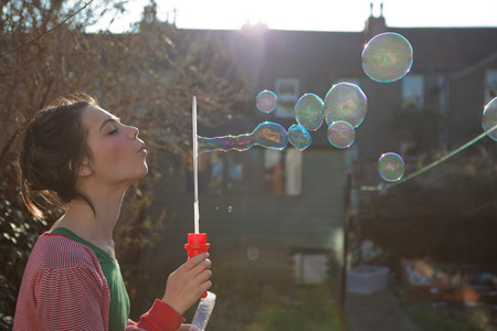 sayings: Young woman blowing bubbles outdoors LANG_EVOIMAGES