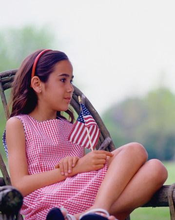 Girl sitting on porch holding US flag LANG_EVOIMAGES