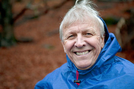Senior man wearing waterproof clothing and smiling
