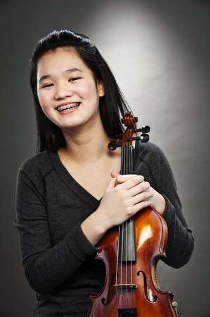 Portrait of young Asian teenage girl holding violin,smiling