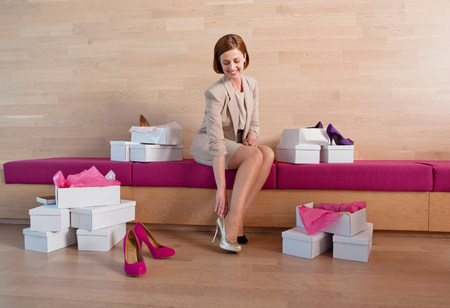 clothing store: Woman trying on shoes in shoe shop