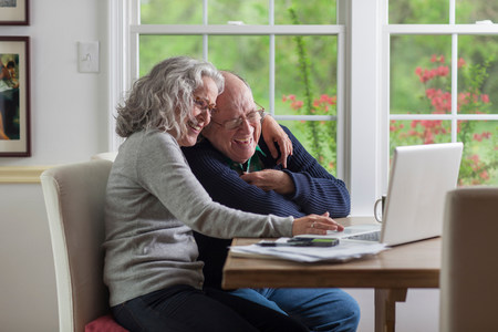 70 75: Senior couple using laptop at home,laughing LANG_EVOIMAGES