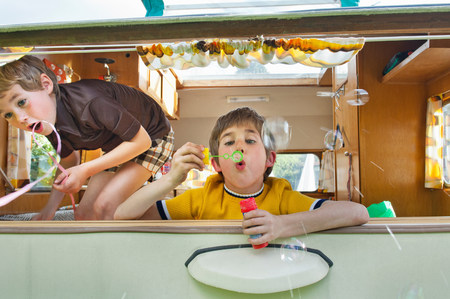 two persons only: Two boys blowing bubbles out of caravan LANG_EVOIMAGES
