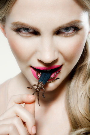 revulsion: Young woman biting plastic beetle LANG_EVOIMAGES
