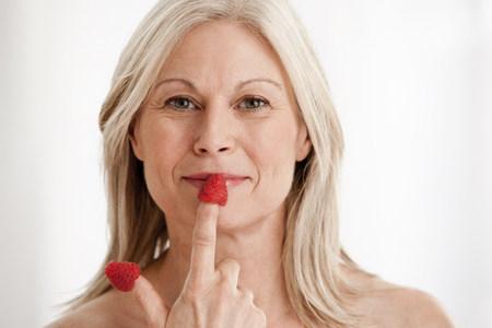 Mature woman wearing raspberries on fingers,portrait