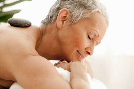 Senior woman receiving stone therapy