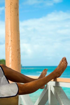 Mann im Urlaub mit den Beinen, die auf Verandaschiene stillstehen LANG_EVOIMAGES