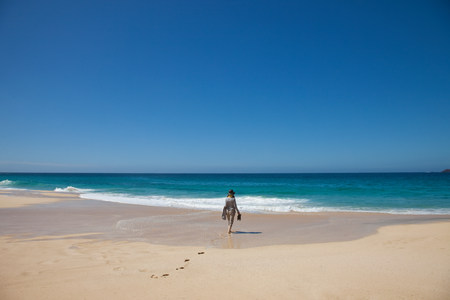 Woman alone on a beach,walking toward the sea LANG_EVOIMAGES