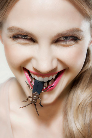 fetishistic: Young woman biting plastic beetle LANG_EVOIMAGES