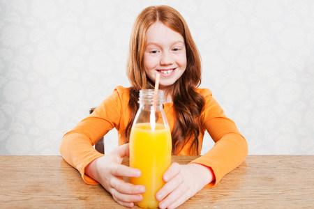 sit down: Girl with bottle of orange juice LANG_EVOIMAGES