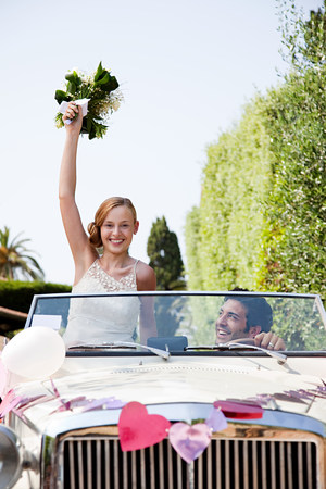 new age: Newlyweds in classic car, bride holding bouquet LANG_EVOIMAGES