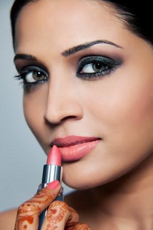 indian subcontinent ethnicity: Beautiful woman applying lipstick