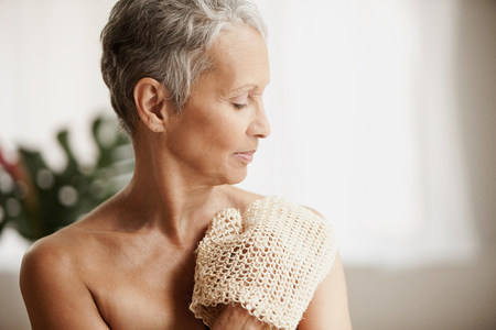 half naked: Senior woman exfoliating with mitt LANG_EVOIMAGES