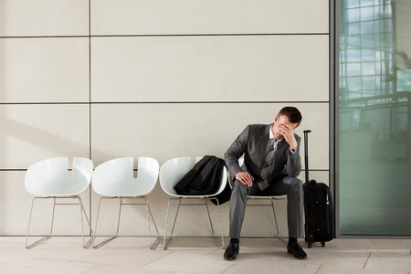 fedup: Businessman waiting with luggage and head in hands