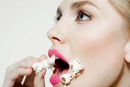 sobredosis: Joven mujer comiendo palomitas de maíz