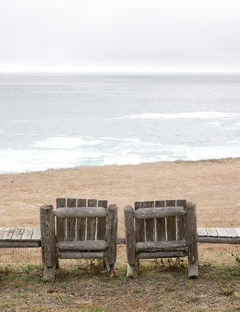 winter escape: Two empty wooden chairs on beach