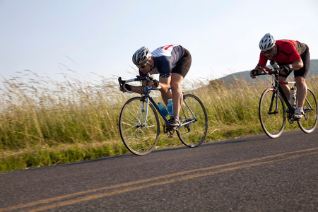 liberating: Two cyclists or road,racing downhill LANG_EVOIMAGES