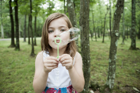 6 9 years: Girl blowing bubbles in forest