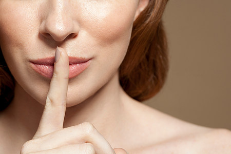Woman with finger on lips,close up