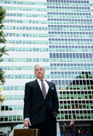low self esteem: Businessman with briefcase in front of glass building LANG_EVOIMAGES