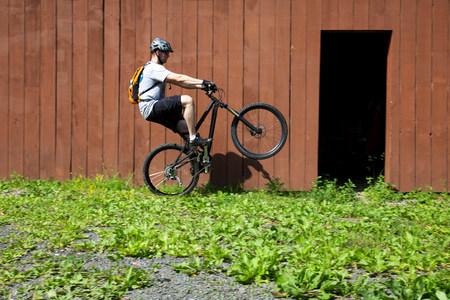 Mountain biker riding on one wheel outside barn