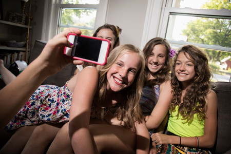untruth: Group of girls being photographed with camera phone