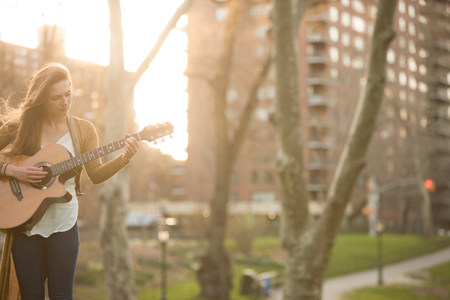 towerblock: Young woman playing guitar in the park