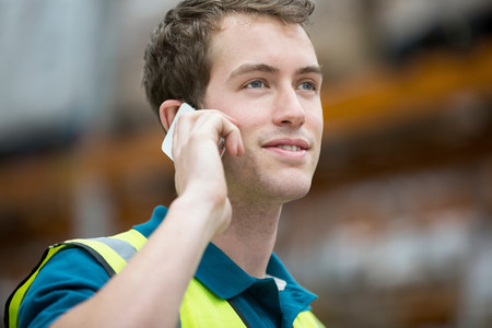 Man on cell phone in warehouse,portrait