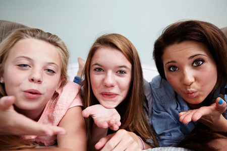 puckered: Three teenage girls blowing a kiss LANG_EVOIMAGES