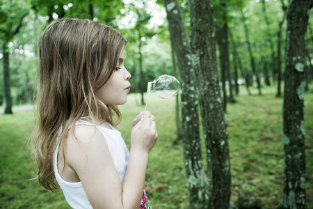 off shoulder: Girl blowing bubbles in forest