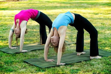Two women bending over backwards on yoga mats outdoors LANG_EVOIMAGES